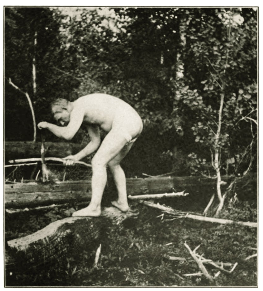 a man crouches naked in the woods in an old black and white photo
