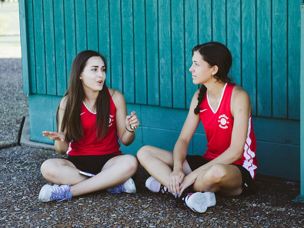 teen girls sitting cross-legged on the ground