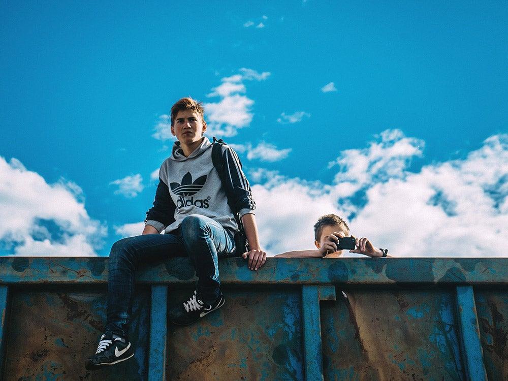 teens sitting on a wall