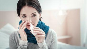 A woman administers a nasal spray