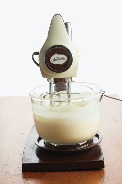 A Sunbeam stand mixer working on a glass bowl of cake batter.