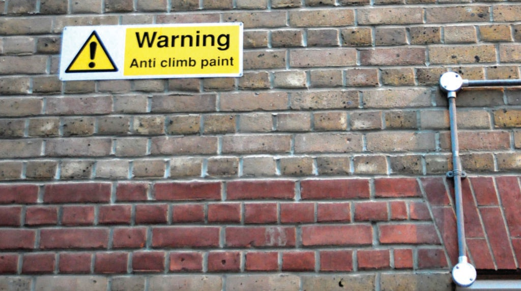 A brick wall covered in anti-climb paint.