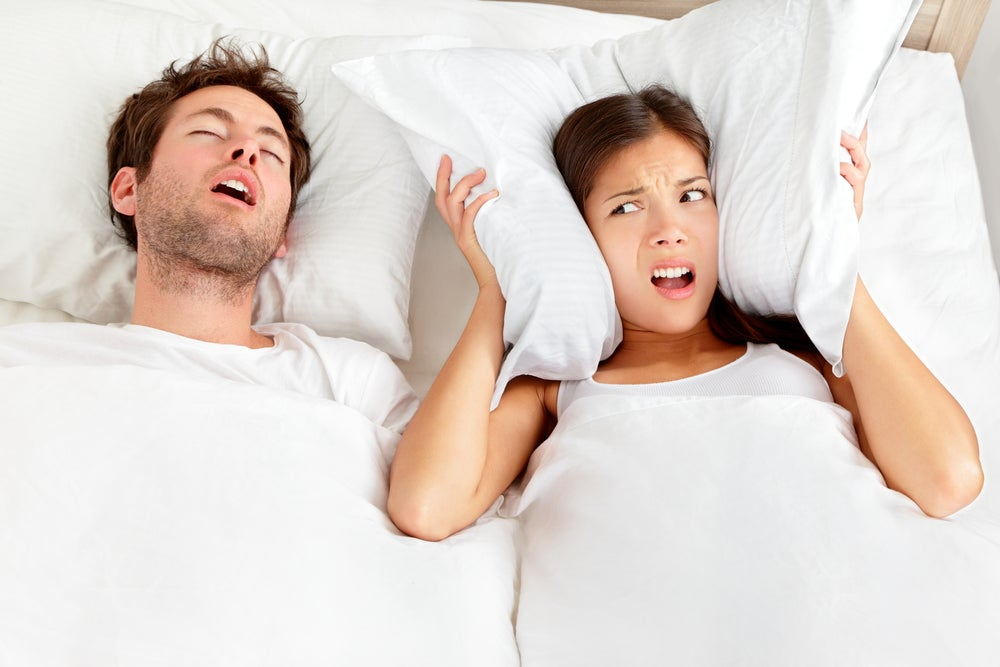 A man snoring in a white bed, while a woman angrily holds a pillow over her ears next to him.