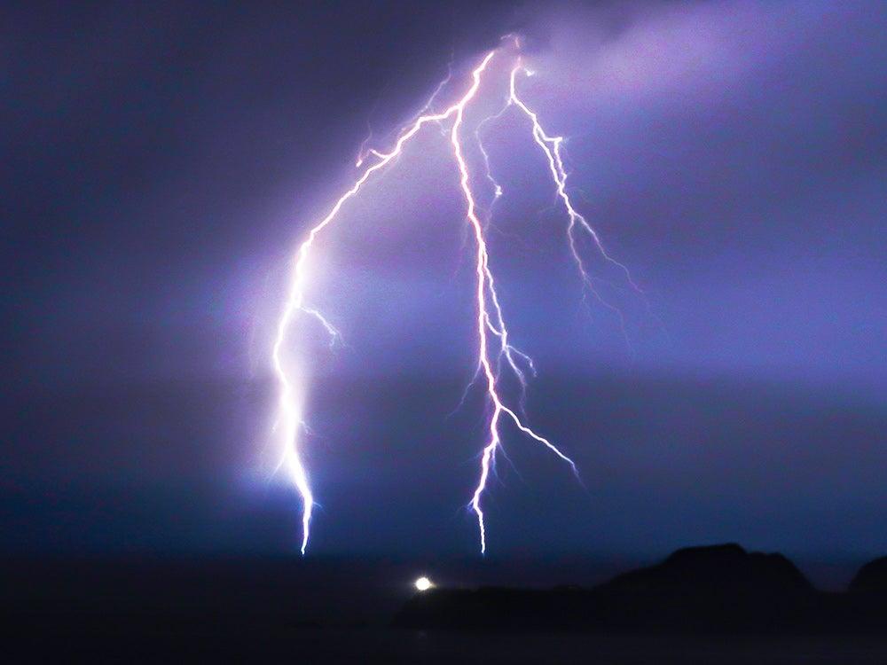 bright lightning against purple sky