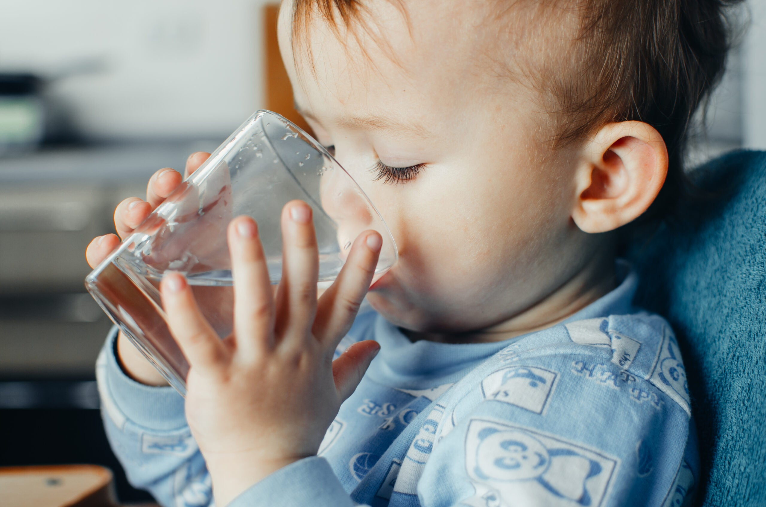 a baby drinking a glass of water
