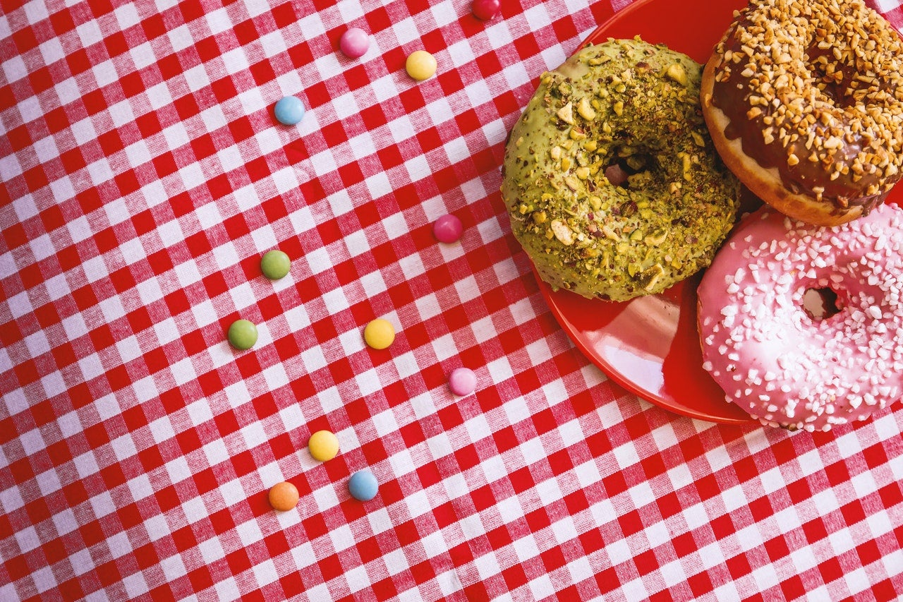 Three donuts on a checkered tablecloth