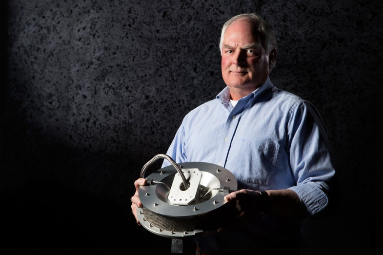 Jim Harris holding the final iteration of the Touch-And-Go Sample Acquisition Mechanism.