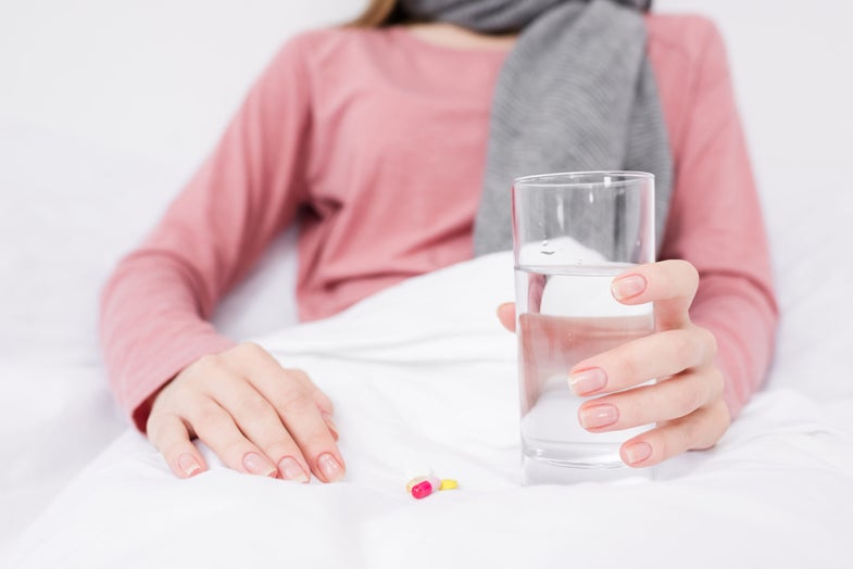 woman in bed with pills