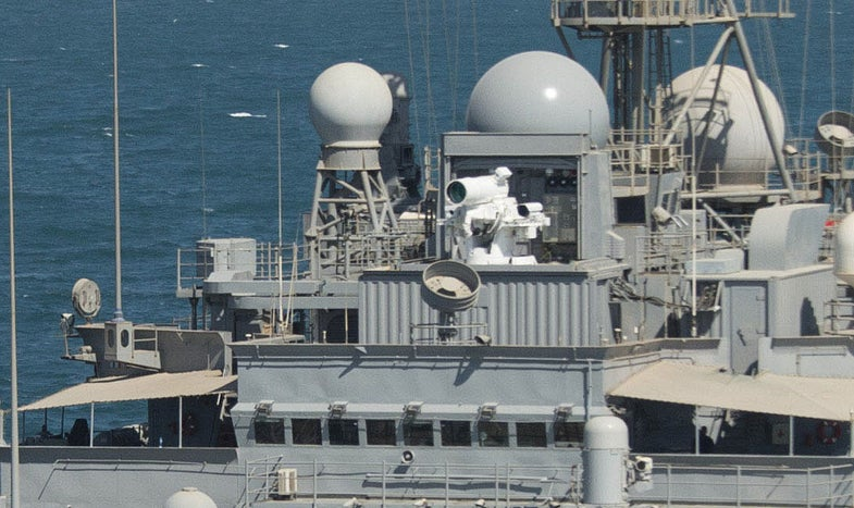 Detail of the Laser Weapon System (LaWS) on the USS Ponce. The laser gun is a white cylinder on top of a gray ship.