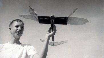boy holding a model plane