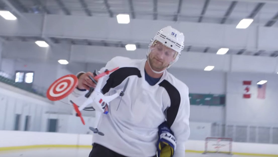 Watch a hockey player shoot down target drones with pucks