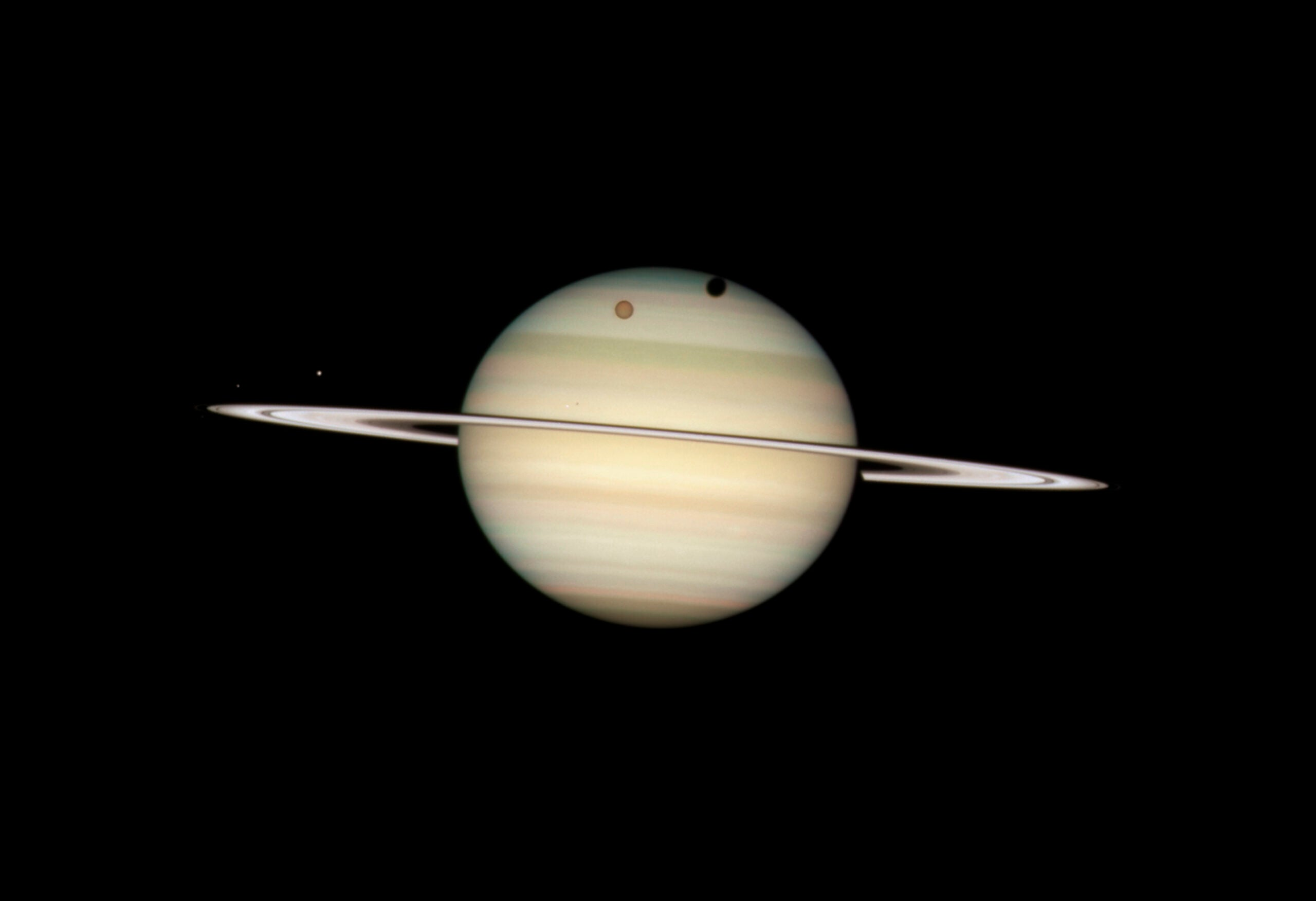 The planet Saturn, viewed nearly edge-on, with four of its moons visible in the foreground