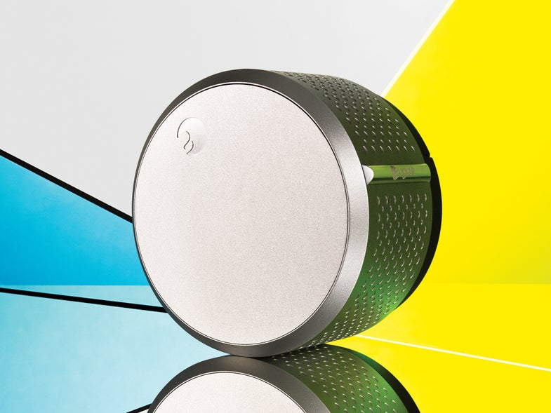 The silver cylinder of the August Smart Lock with yellow and blue in the background