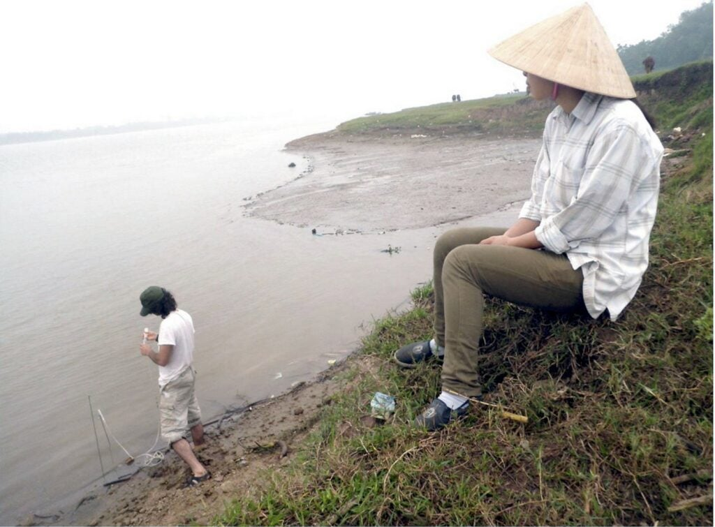 High concentrations of arsenic are making their way from the Red River into aquifers near Hanoi, Vietnam, a new study shows. Mason Stahl, in the water, and a colleague test water at the river's edge where sediment is being deposited. Source: Courtesy of M