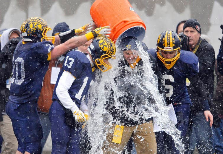 football players pouring water on coach