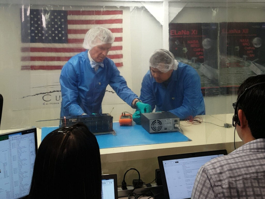 In a clean room, Bill Nye helps engineers prep LightSail 2 for testing.