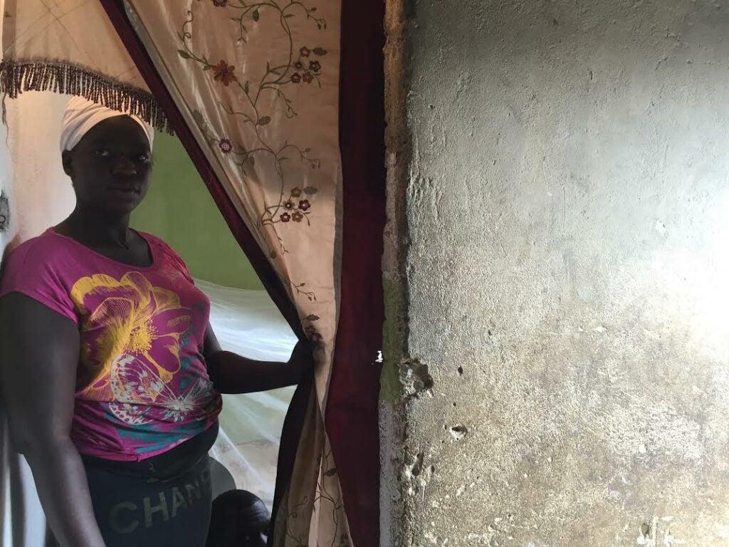 Calunga leans against a doorway in Luanda, Angola.