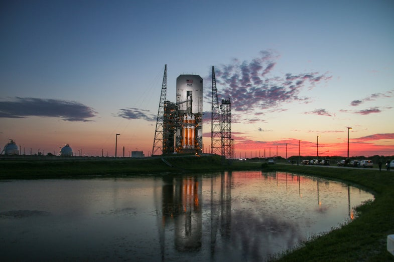 Delta IV Heavy on a launch pad with the sun setting in the background