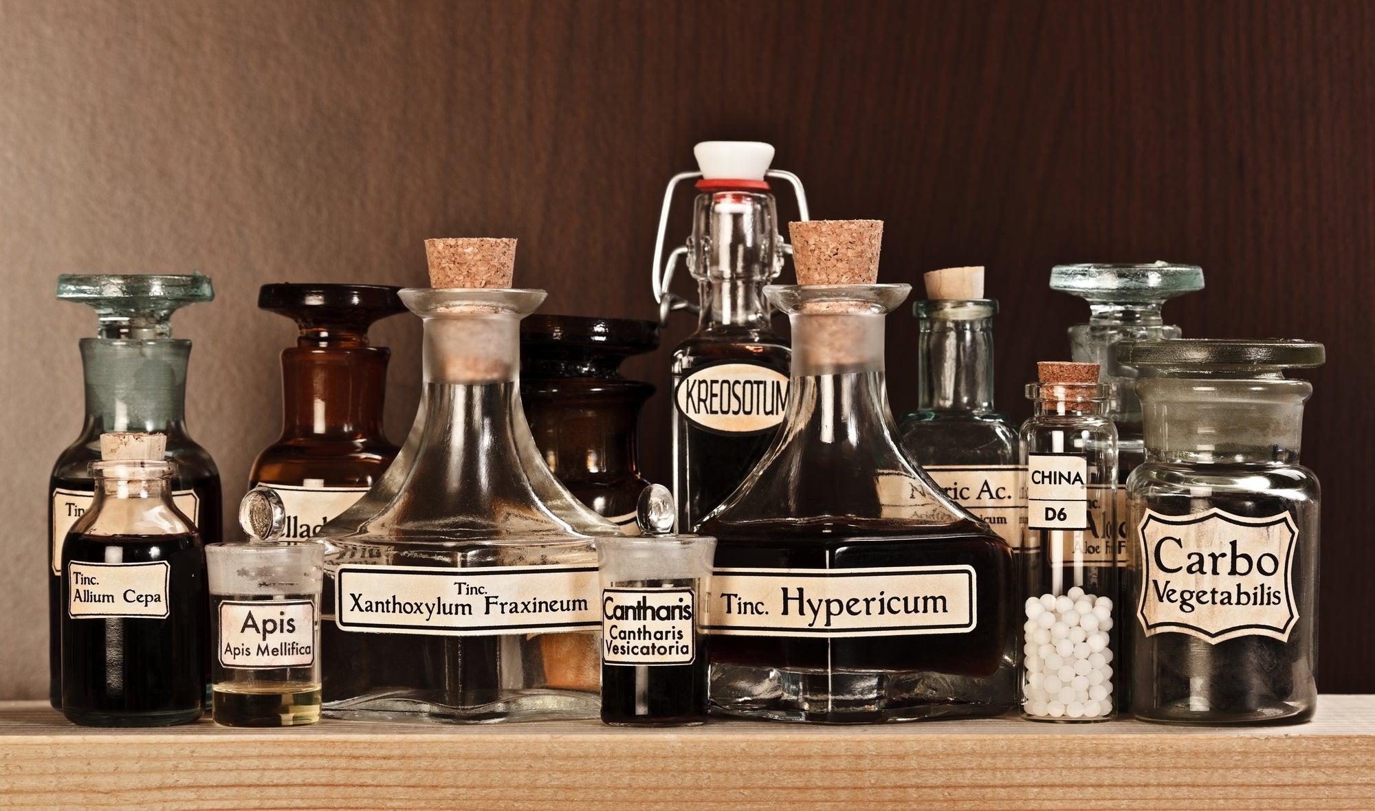 glass bottles on a shelf with handwritten labels