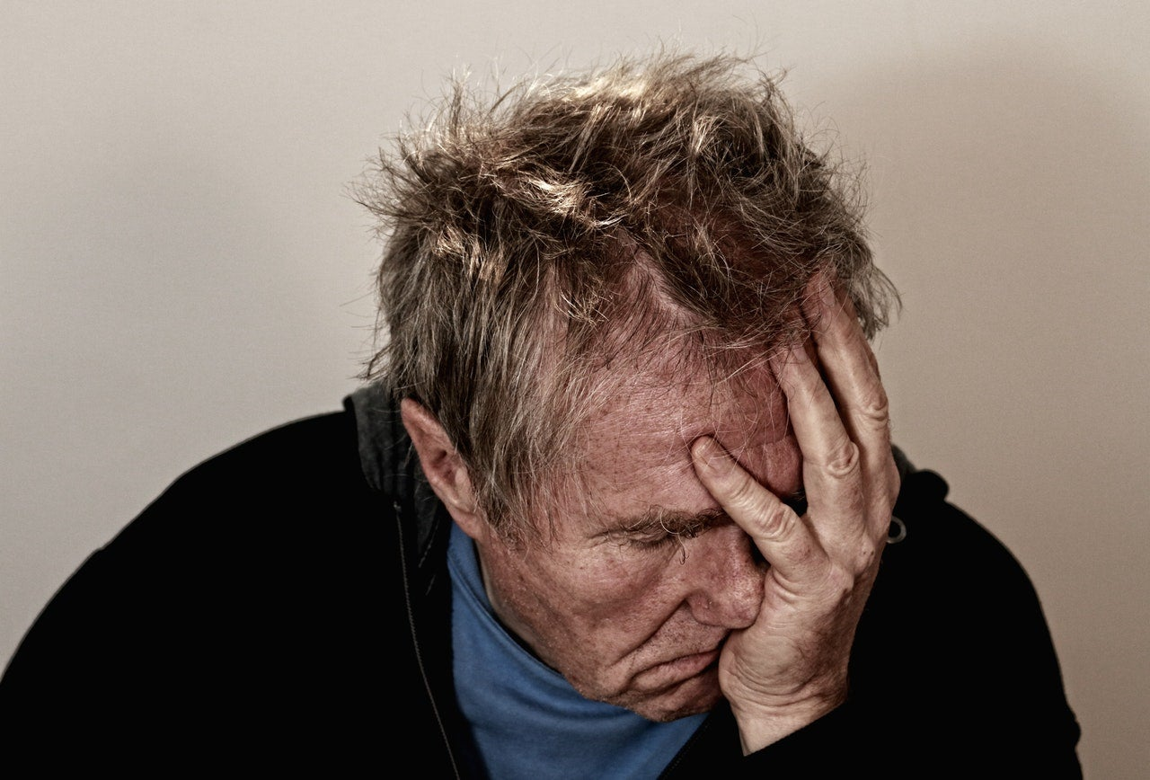 a man holding his head in pain, perhaps because he is sick
