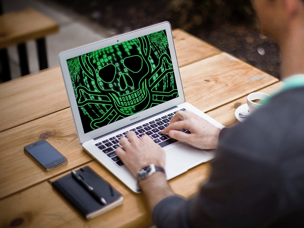 A person sitting in front of a laptop that has a skull and crossbones in green code on the screen.