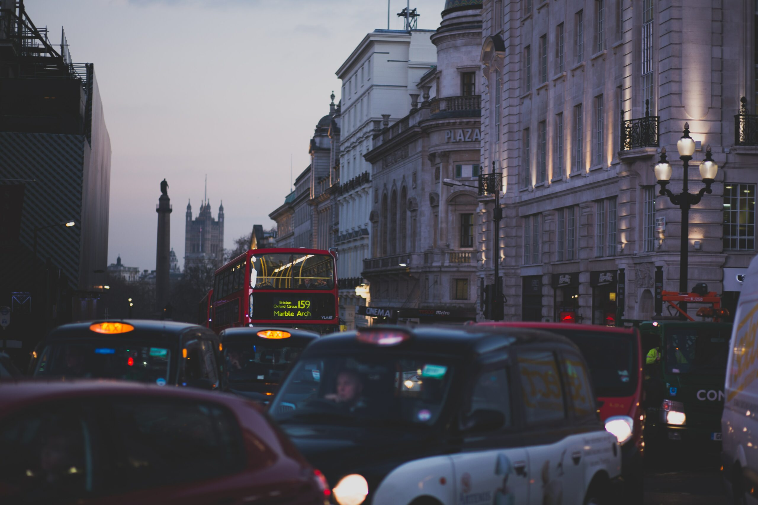 Cars and buses on busy London street at dusk.
