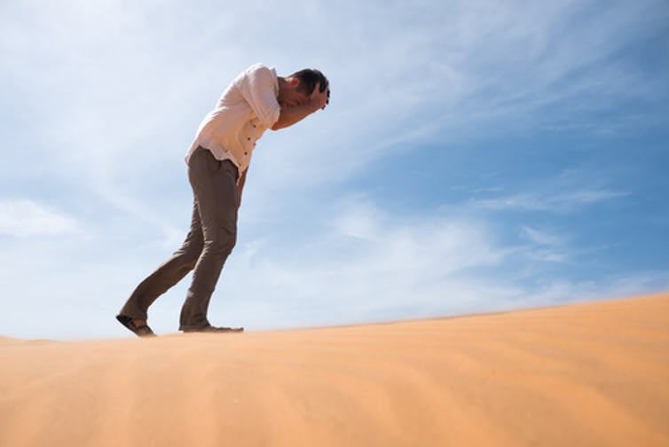 man walking in the desert clutching his head