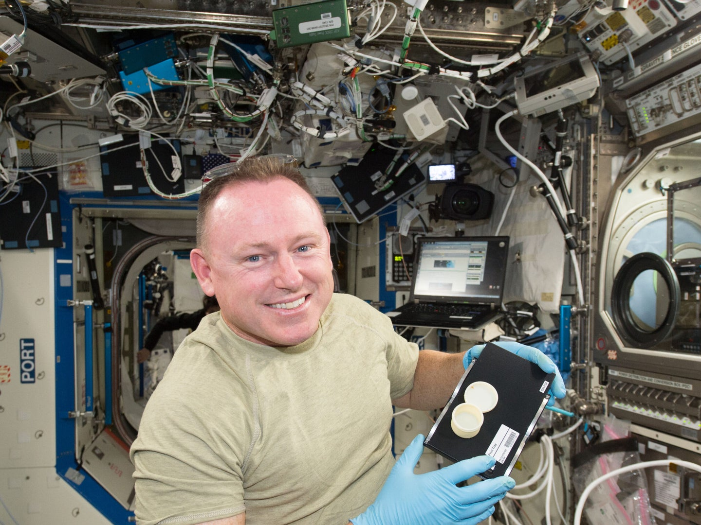 Astronaut Butch Wilmore holds a container that was 3D printed on the International Space Station.