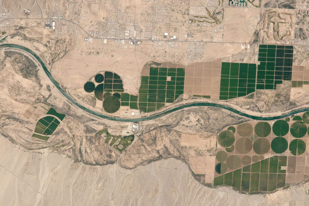 Along a stretch of the Colorado River, patches of green agriculture pop against the dry dessert.