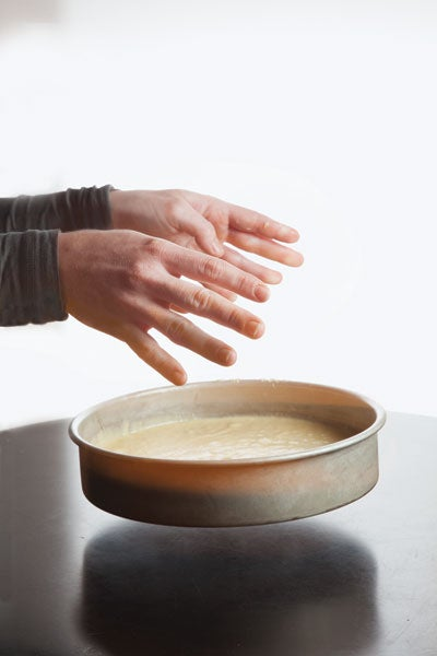 A person dropping cake batter in a cake pan onto a hard surface, like a counter.