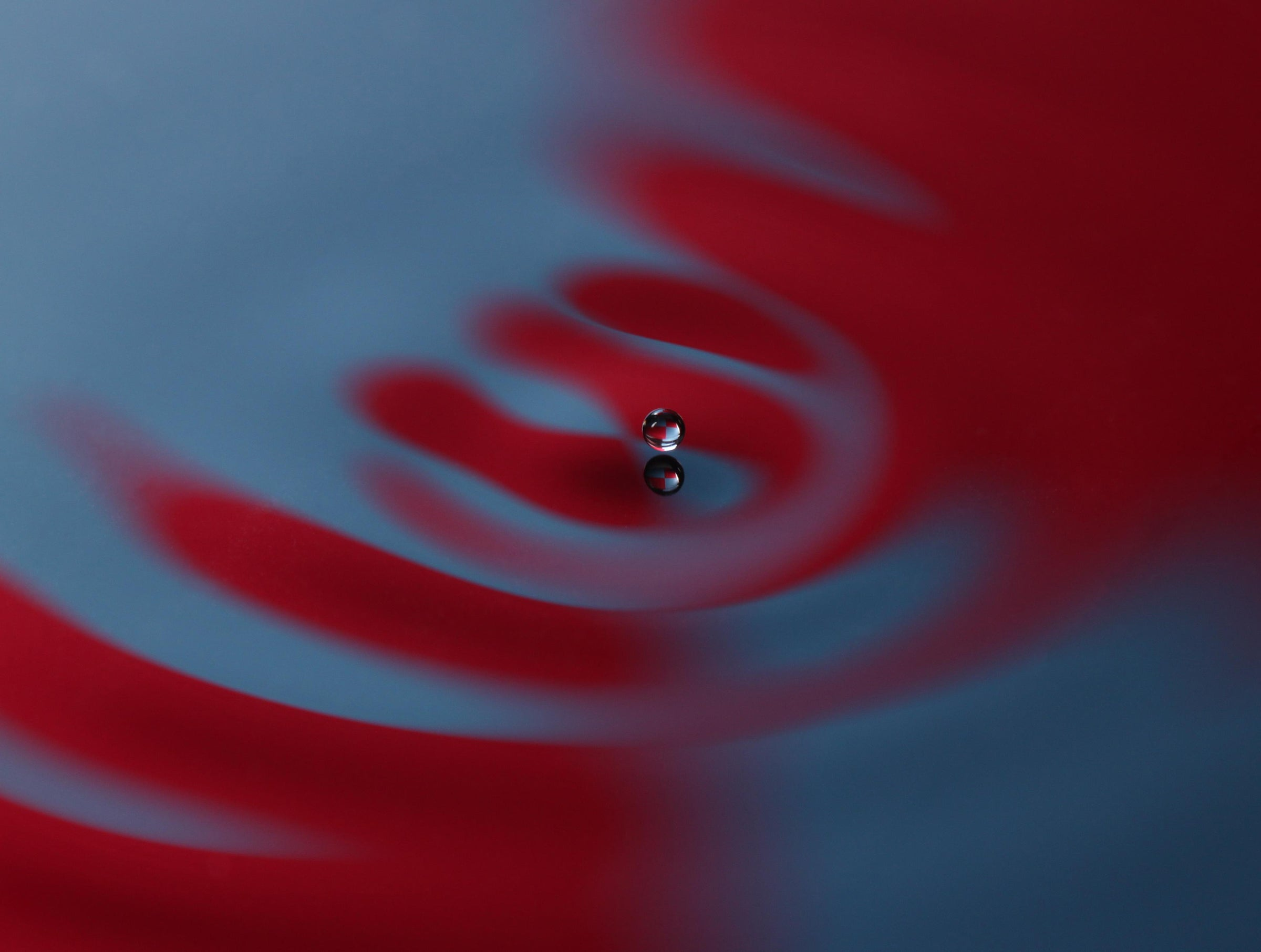 a droplet bounces across a red and blue water surface