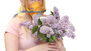 a woman holding flowers and wearing a gas mask