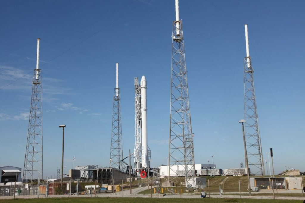 man standing next to rocket, zoomed out