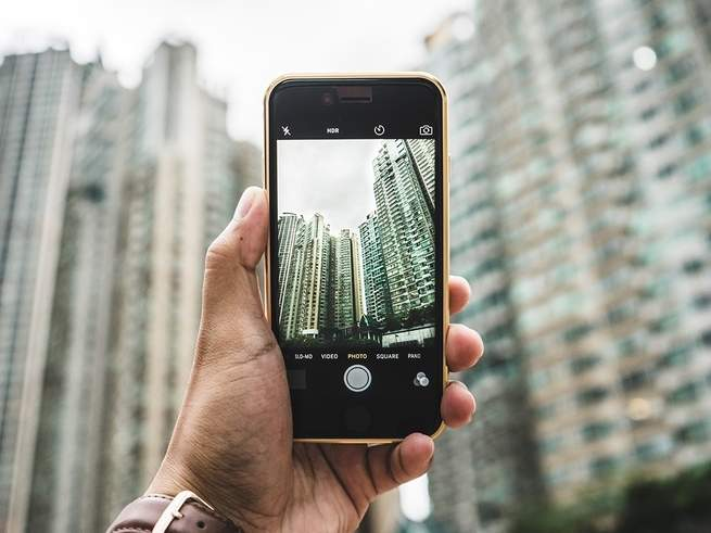 A person holding an iPhone and looking through the camera app at some tall buildings.