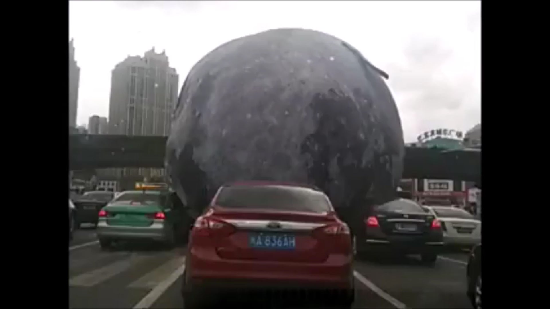 Watch An Inflatable Moon Roll Over Traffic Thanks To A Typhoon