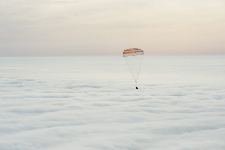 Soyuz Capsule landing with a parachute over the clouds