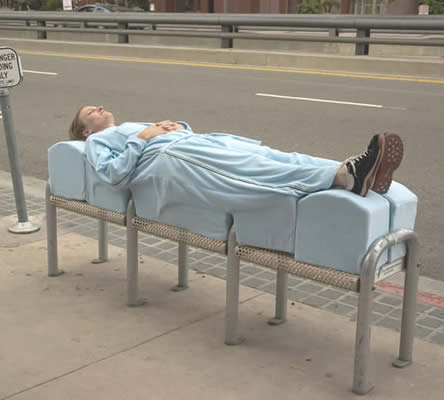 A woman lies on a bench designed to deter lying down by wearing an special suit designed by artist Sarah Brown