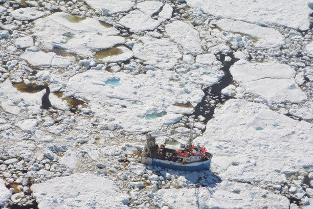 fishing boat surrounded by sea ice