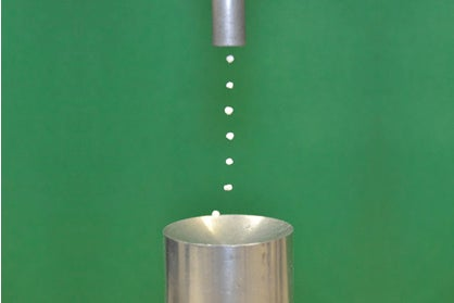 photo showing an acoustic levitator levitating seven Styrofoam bits in a column