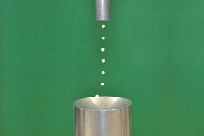 photo showing an acoustic levitator levitating seven Styrofoam bits in a column