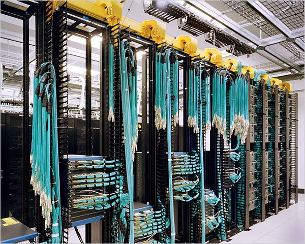 data center room with blue cables and shelves