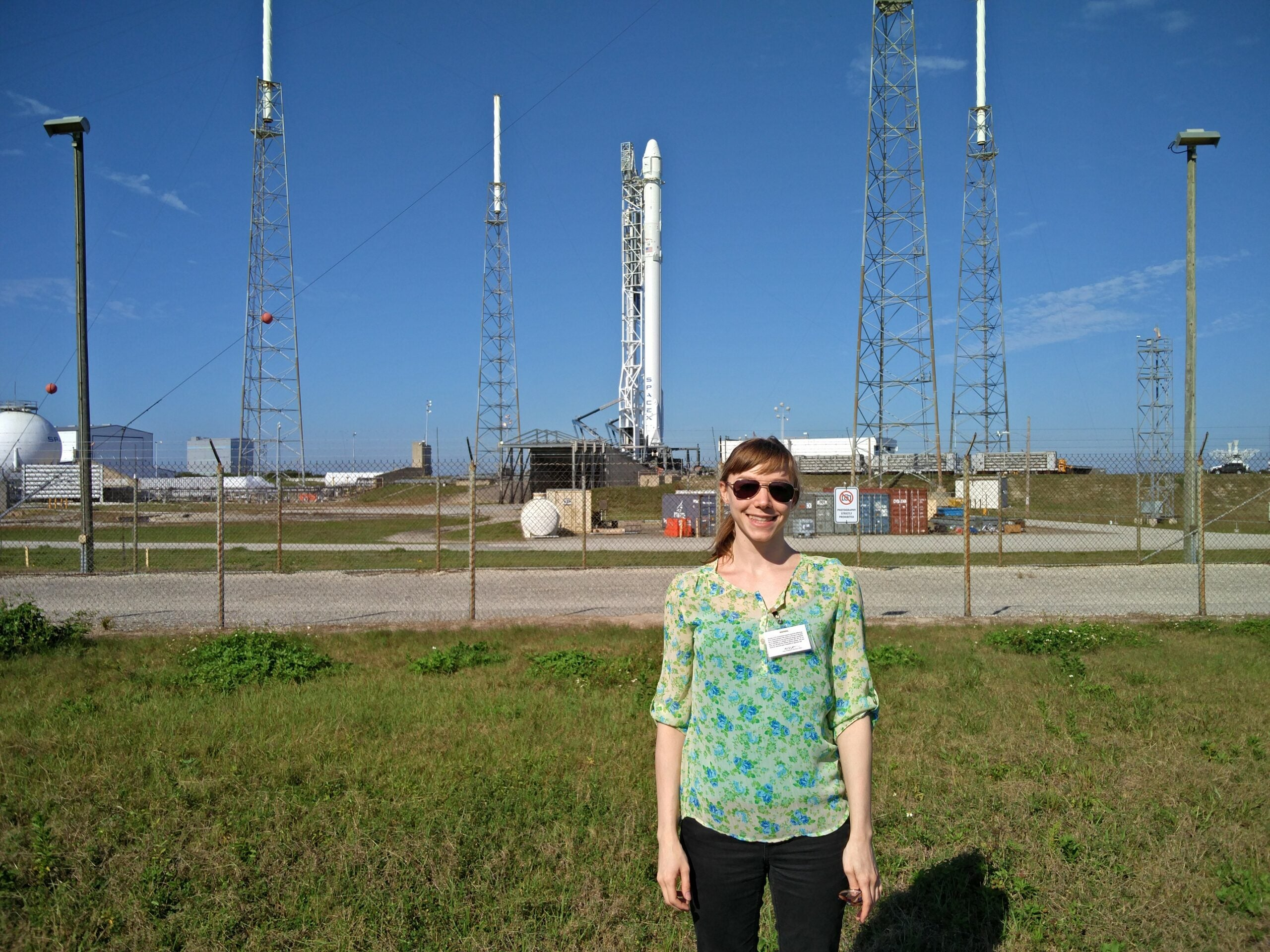 popular science editor poses for a picture in front of the falcon 9