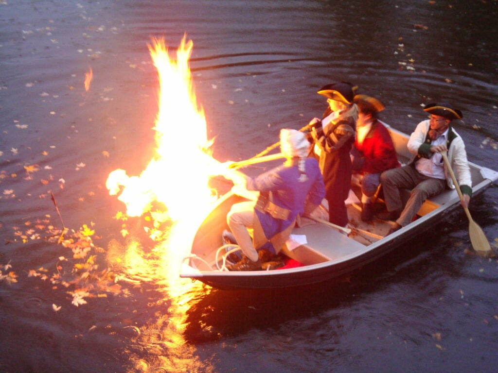 men in Revolutionary War clothing light marsh gas on fire