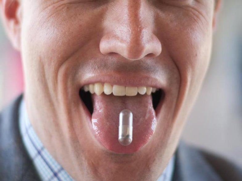 Christopher Bettinger displaying an edible battery made with melanin and dissolvable materials on his tongue.