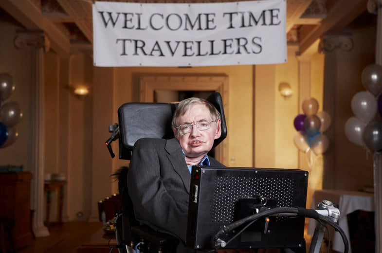 """stephen hawking sits in front of a sign that says """"Welcome Time Travelers"""""""