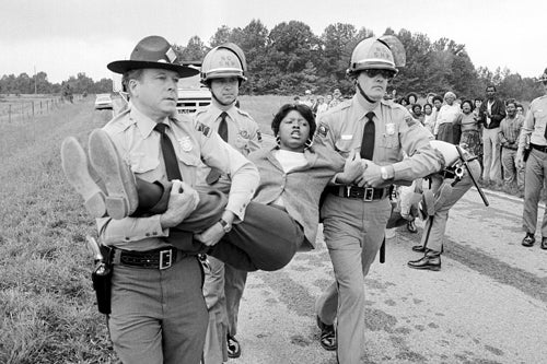 A woman is carried away by police during a protest.