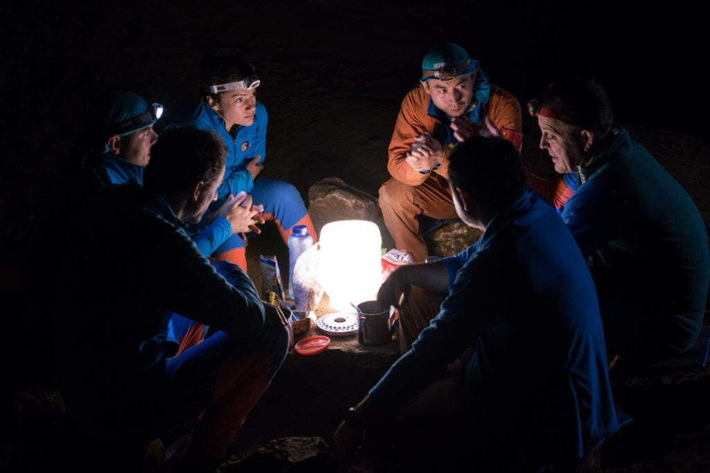 astronauts sit around light, eating