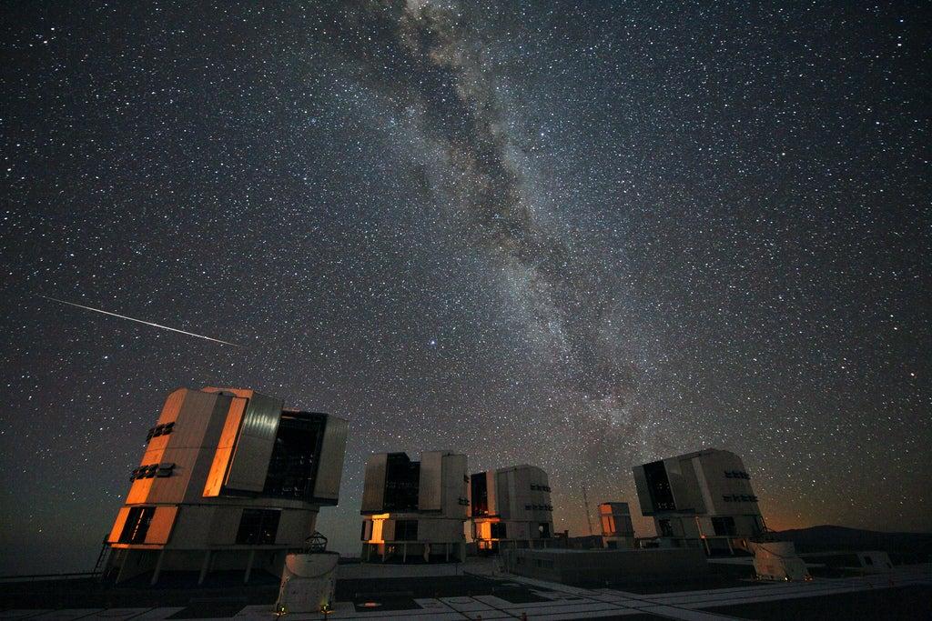 starry night sky above telescopes on hill