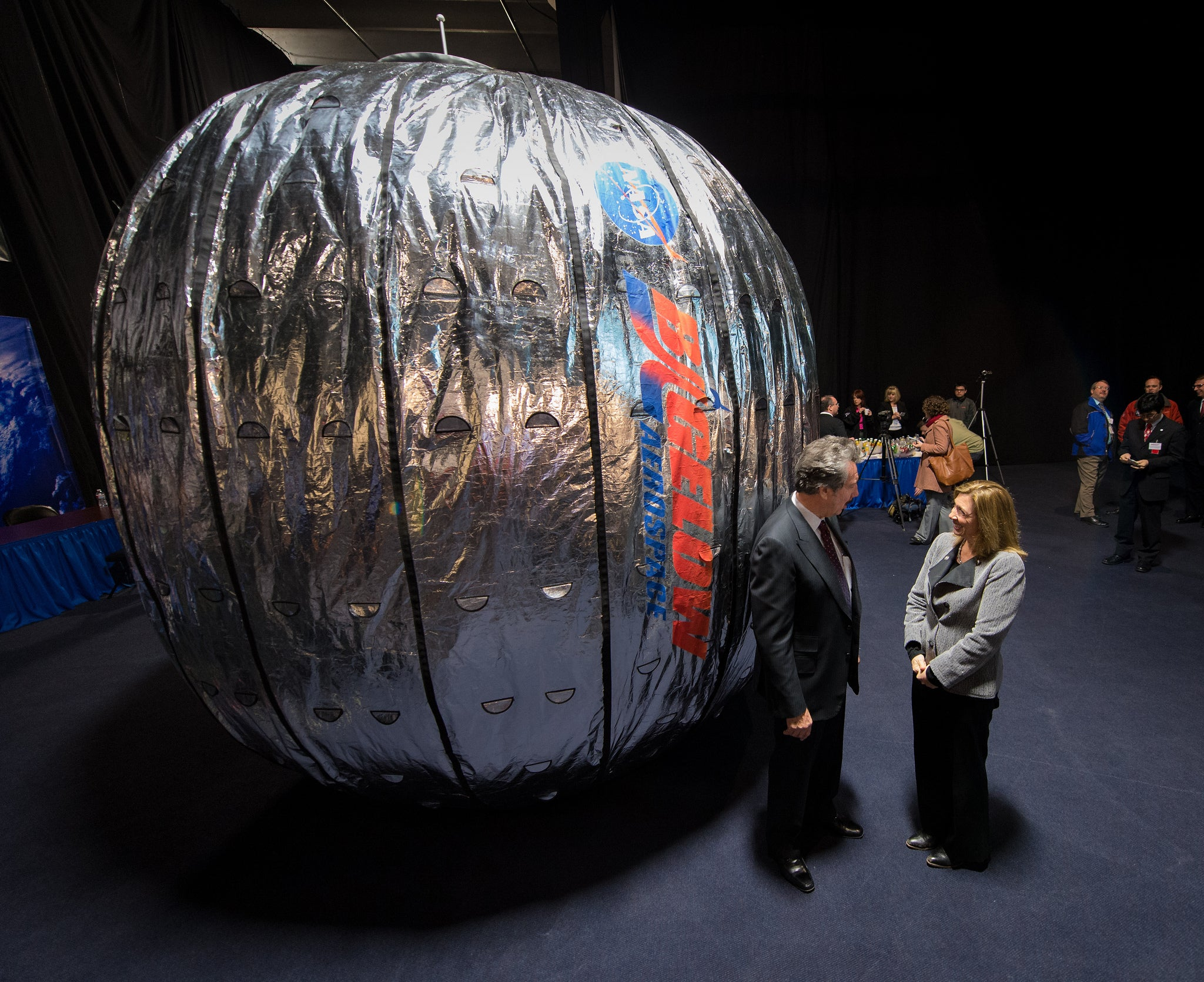 two people stand next to BEAM module