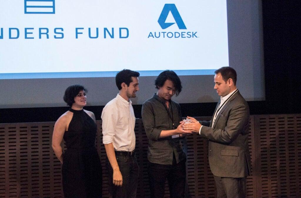 Daniel Grushkin awards the glass microbe to Fashion Institute of Technology
